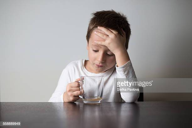 Bored boy holding empty cup of tea