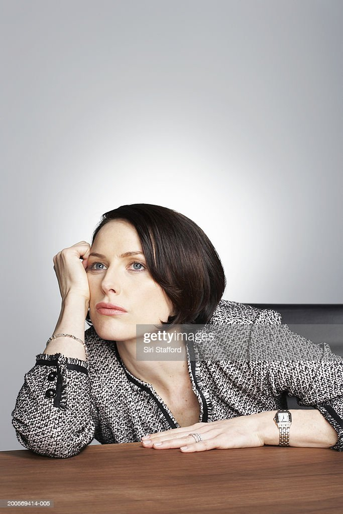 Bored business woman sitting at desk : Stock Photo