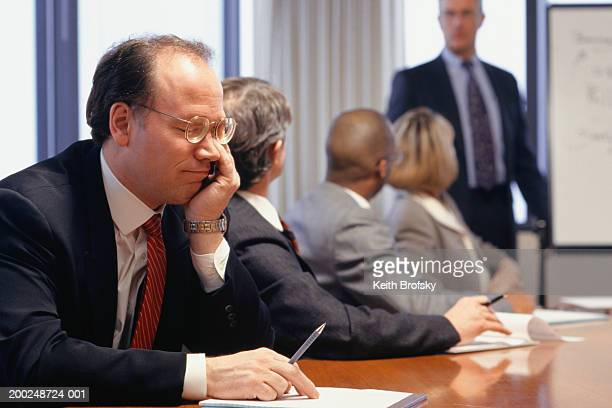 Bored businessman at meeting in conference room