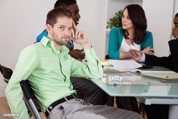 Bored businessman looking back during office business meeting