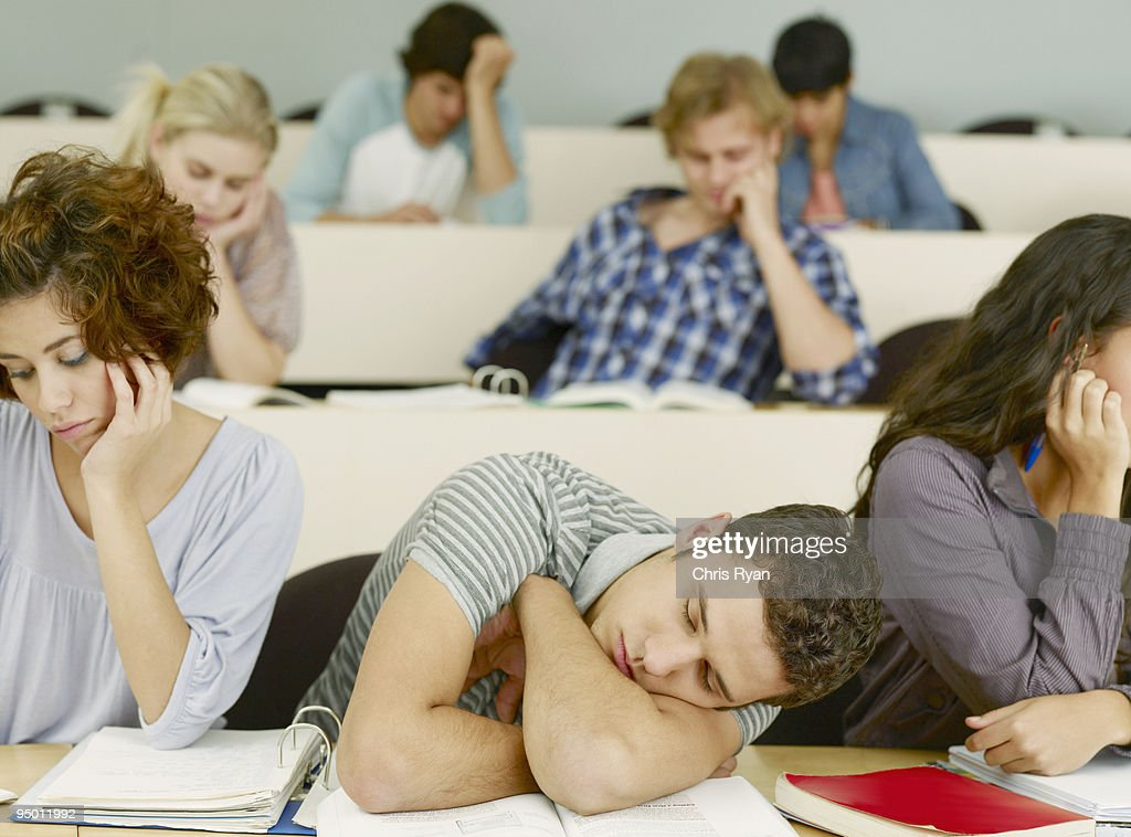Bored college students sleeping in lecture hall : Stock Photo