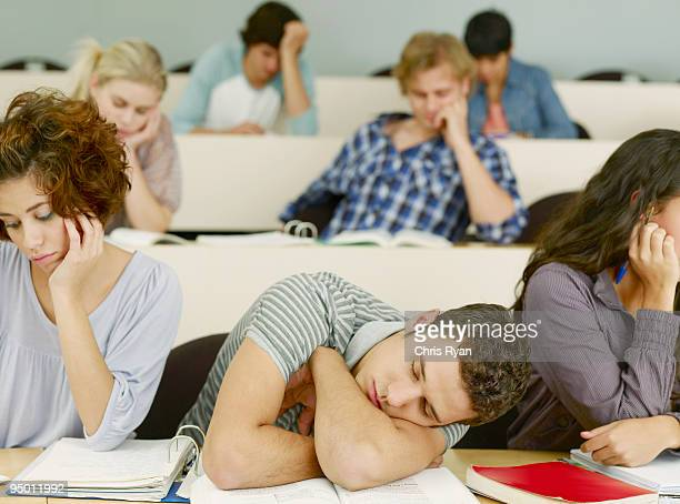 Bored college students sleeping in lecture hall