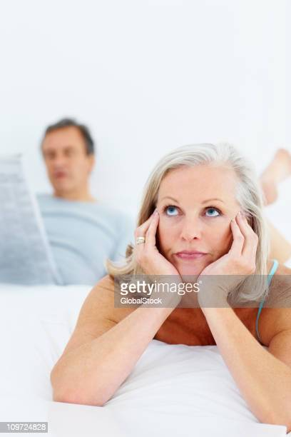 Bored elderly woman in bed with man at the back