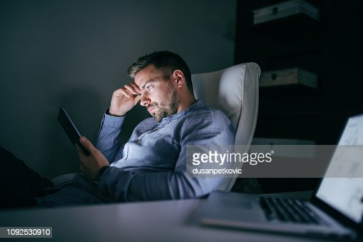 Bored employee sitting in the office late at night and using tablet. Side view. : Stock Photo