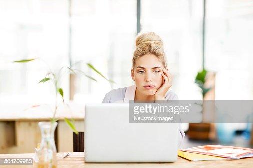 Bored Female Entrepreneur Using Laptop At Desk