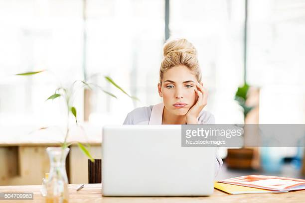 Bored Female Entrepreneur Using Laptop At Desk