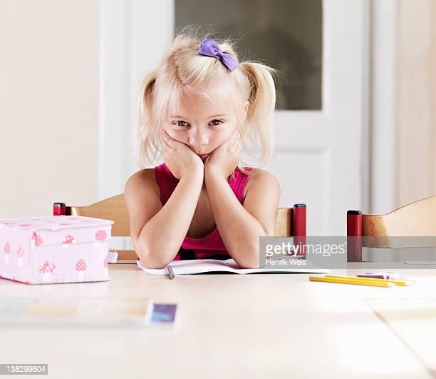 Bored girl doing homework at table