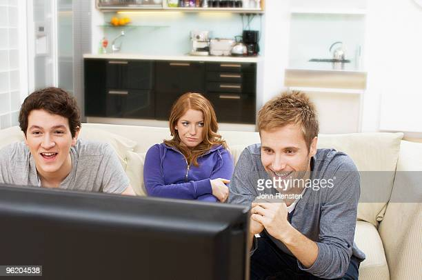 bored girl ignores tv while guys are oblivious