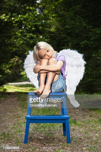 Bored girl in wings sitting on stool