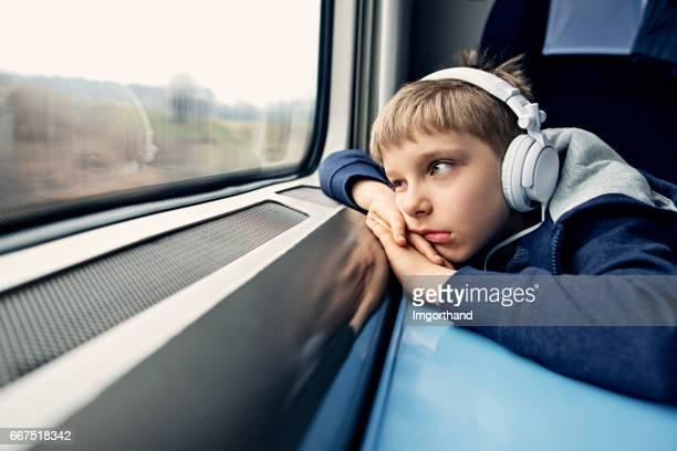 Bored little boy travelling on train