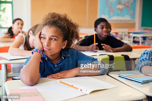 Bored little girl in elementary classroom. : Stock Photo