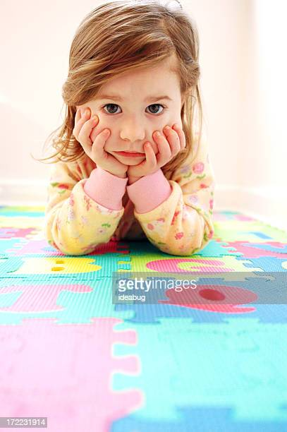 Bored Little Girl Lying on Floor Looking at Camera