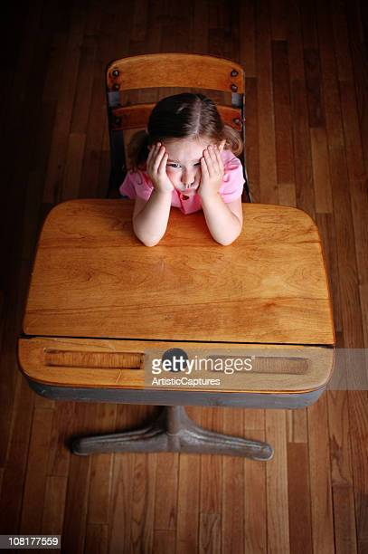 Bored Little Girl Sitting at Classroom Desk