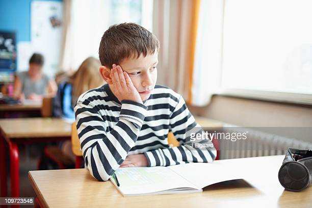 Bored little school boy in classroom looking out of window