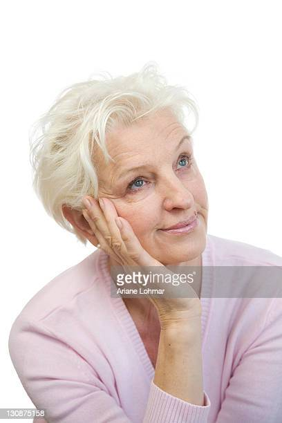 A bored mature woman rests her head on her hand and rolls her eyes