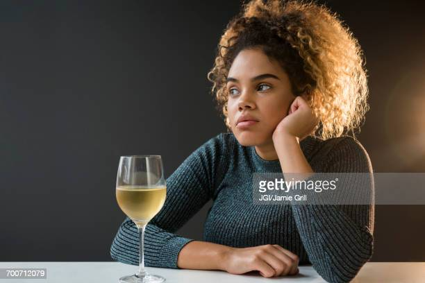 Bored Mixed Race woman wearing sweater drinking wine