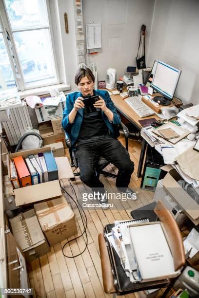 Bored Office Worker Taking Selfie In Messy Office