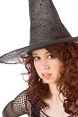 Portrait of Latina teenager girl in black Halloween hat and fishnet dress