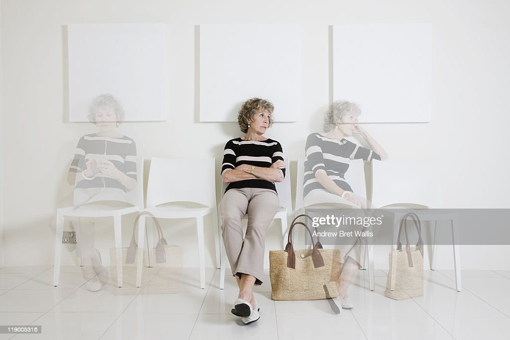 Bored senior woman passing time in a waiting room