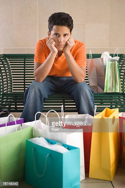 Bored Teenage Boy with Many Shopping Bags