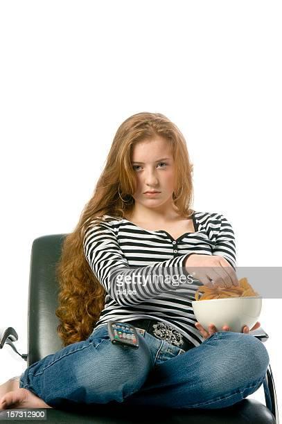 bored teenage girl eating potato chips