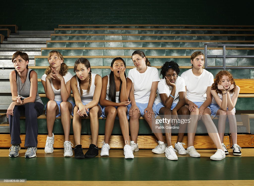 Bored teenage girls (12-16) sitting with instructor in gym class : Stock Photo