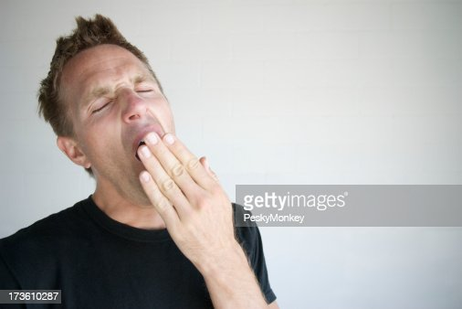 Bored Tired Man in Black T-Shirt Yawning Covering Mouth
