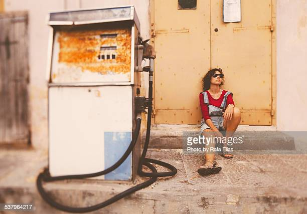 Bored woman sitting next to gas pump