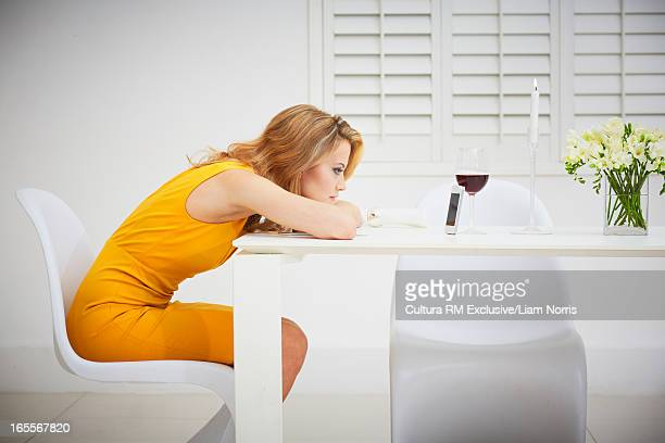 Bored woman using cell phone at table