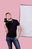 Bored young male photographer holding camera over pink background