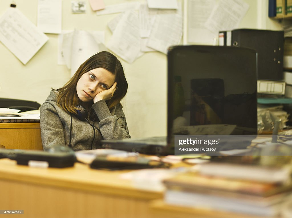 Bored young woman at desk leaning on elbow