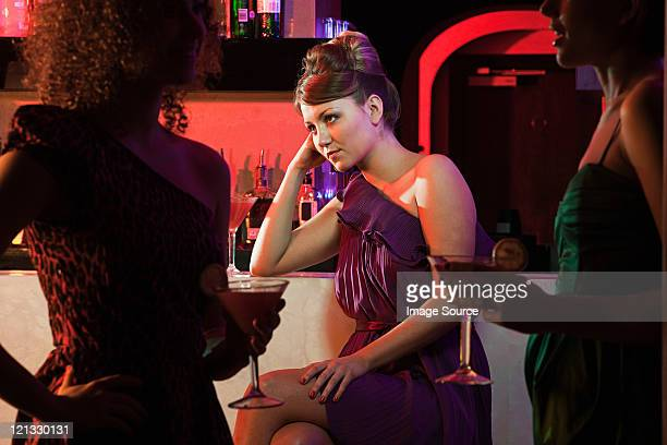 Bored young woman sitting at cocktail bar