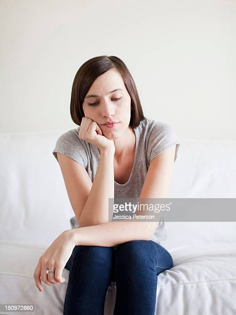 Bored young woman sitting on bed