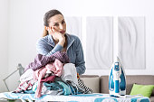 Disappointed unhappy housewife leaning on a pile of laundry on the ironing board