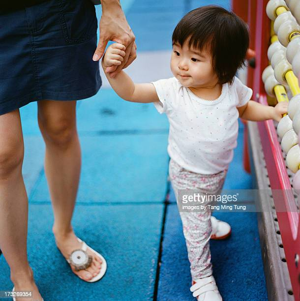 Boring looking toddler playing with giant abacus.