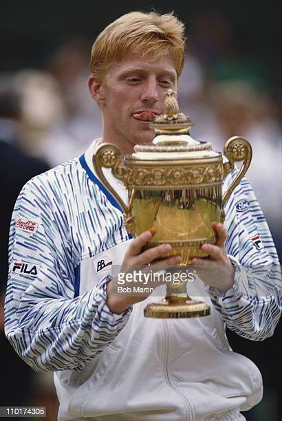 Boris Becker looks at the names of the past winners as he holds the trophy after defeating Stefan Edberg at the Wimbledon Lawn Tennis Championship...