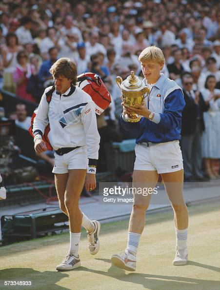 Boris Becker of Germany looks at the names engraved on the trophy as he walks off court with Kevin Curren after defeating him in the Men's Singles...