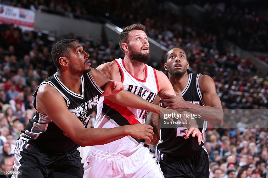 Boris Diaw and Kawhi Leonard of the San Antonio Spurs boxes out Joel Freeland of the Portland Trail Blazers on December 15 2014 at the Moda Center...