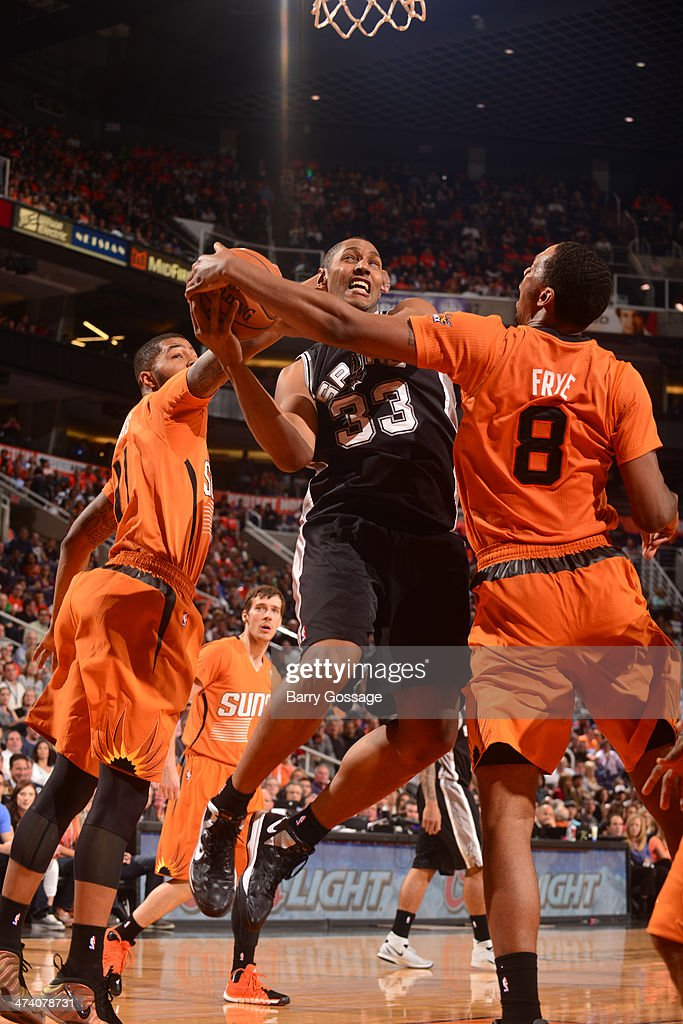 Boris Diaw #33 of the San Antonio Spurs drives against Channing Frye #8 and Markieff Morris #11 of the Phoenix Suns on February 21, 2014 at U.S. Airways Center in Phoenix, Arizona.