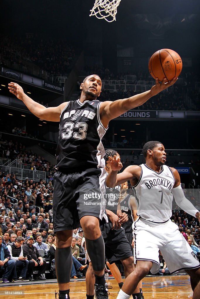 Boris Diaw #33 of the San Antonio Spurs grabs a rebound against Joe Johnson #7 of the Brooklyn Nets on February 10, 2013 at the Barclays Center in the Brooklyn borough of New York City.