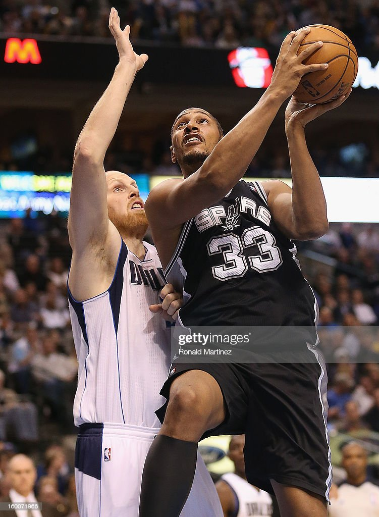 Boris Diaw #33 of the San Antonio Spurs takes a shot against Chris Kaman #35 of the Dallas Mavericks at American Airlines Center on January 25, 2013 in Dallas, Texas.
