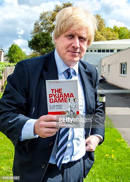 Boris Johnson holds up a copy of 'The Pyjama Game A Journey into Judo' which had been written by his editor Mark Law when he worked as a reporter at...