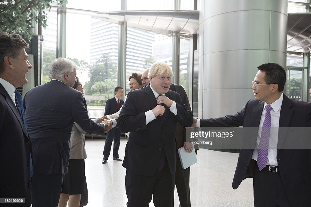 <a gi-track='captionPersonalityLinkClicked' href=/galleries/search?phrase=Boris+Johnson&family=editorial&specificpeople=209016 ng-click='$event.stopPropagation()'>Boris Johnson</a>, mayor of London, center, adjusts his tie as he greets Victor Li, deputy chairman of Cheung Kong (Holdings) Ltd., right, at the Cheung Kong Center in Hong Kong, China, on Friday, Oct. 18, 2013. Johnson is in China as part of a delegation led by Chancellor of the Exchequer George Osborne to boost business links with the worlds second-largest economy. Photographer: Brent Lewin/Bloomberg via Getty Images