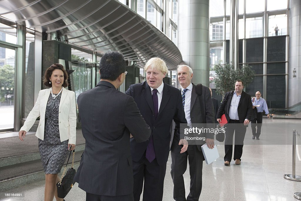 Boris Johnson, mayor of London, center, greets Victor Li, deputy chairman of Cheung Kong (Holdings) Ltd., at Cheung Kong Center in Hong Kong, China, on Friday, Oct. 18, 2013. Johnson is in China as part of a delegation led by Chancellor of the Exchequer George Osborne to boost business links with the worlds second-largest economy. Photographer: Brent Lewin/Bloomberg via Getty Images