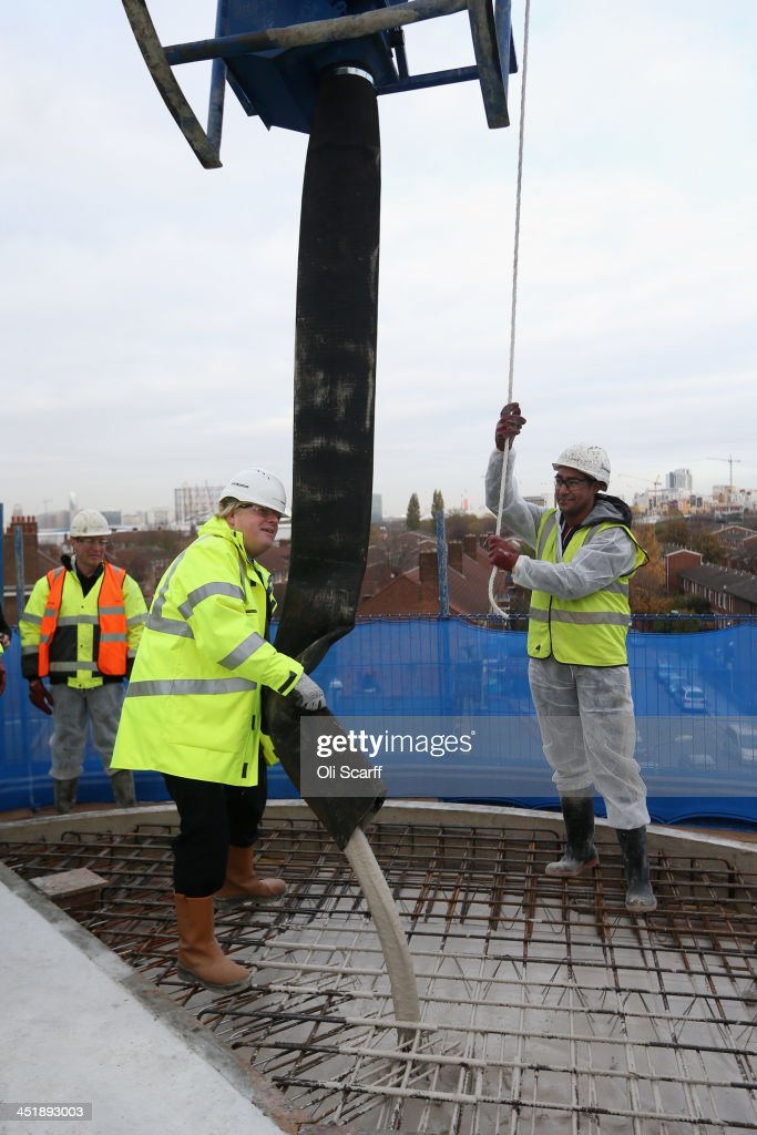 <a gi-track='captionPersonalityLinkClicked' href=/galleries/search?phrase=Boris+Johnson&family=editorial&specificpeople=209016 ng-click='$event.stopPropagation()'>Boris Johnson</a> (C), the Mayor of London, pours concrete from a skip suspended from a crane at the construction site of the 'Greenwich Square' housing development on November 25, 2013 in London, England. Mr Johnson assisted the residential building work, approximately half of which will be low-cost rent or buy accommodation, as he launched his new draft Housing Strategy for the capital. The Mayor aims to address issues around London's rapidly increasing housing needs and in particular the provision of low cost housing.