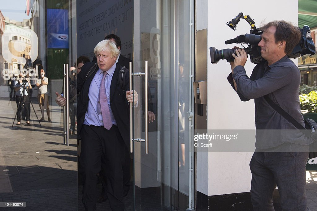 Boris Johnson (L), the Mayor of London, prepares to be interviewed in Leicester Square following his regular 'Ask Boris' phone-in show on LBC talk radio on September 2, 2014 in London, England. Plans for a major new airport to be constructed on an island in the Thames estuary, which have been championed by Mr Johnson and dubbed 'Boris Island', were rejected in a report by the Airports Commission.