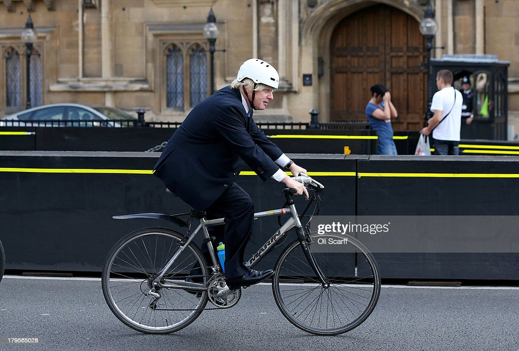 Boris Johnson the Mayor of London rides his bicycle past the Houses of Parliament on September 4 2013 in London England
