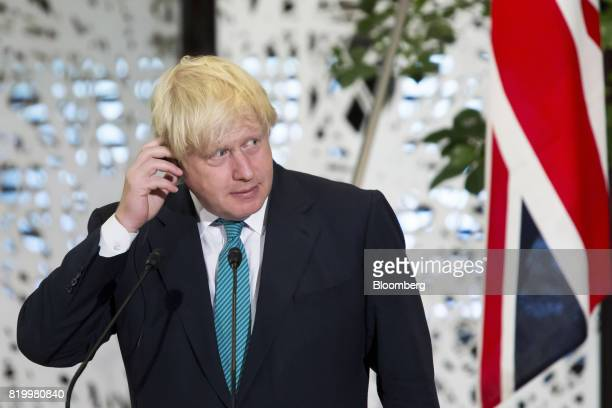 Boris Johnson UK foreign secretary adjusts his ear piece as he listens to Fumio Kishida Japan's foreign minister not pictured delivering a joint...