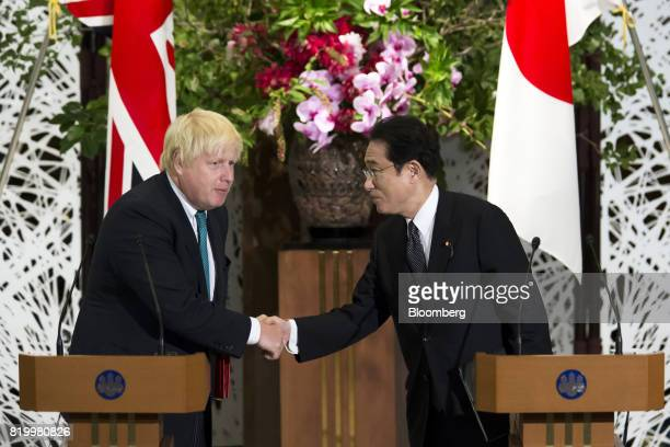 Boris Johnson UK foreign secretary left shakes hands with Fumio Kishida Japan's foreign minister after delivering a joint statement after their...