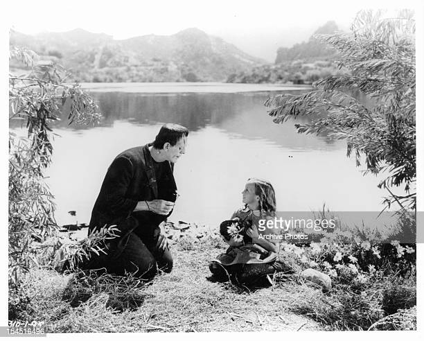 Boris Karloff as the monster sitting lakeside with little girl in a scene from the film 'Frankenstein' 1931